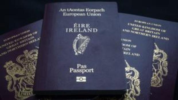 An Irish passport is seen on top of a pile of UK passports