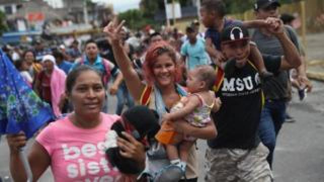 Families in the migrant caravan celebrate after forcing open a gate at the Guatemala-Mexico border