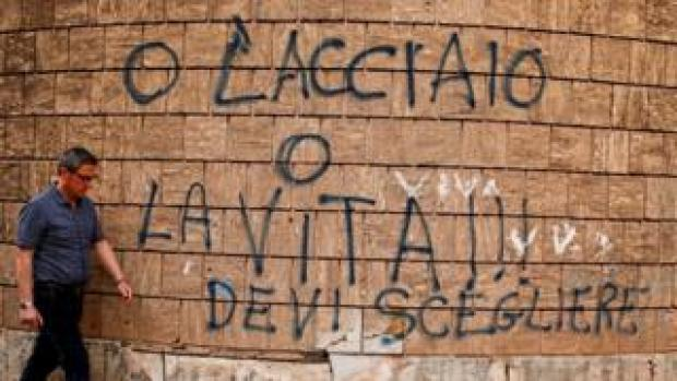 """A man in Taranto, Italy, walks past graffiti reading: """"Steel or life, you have to choose."""" It is a reference to the high-polluting Ilva steel plant in Taranto, 27 April 2018"""