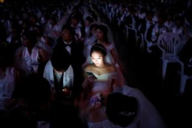 Couples attend a mass wedding ceremony of the Unification Church