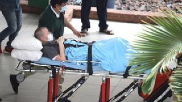 Stephen Cameron, face blurred, leaves hospital