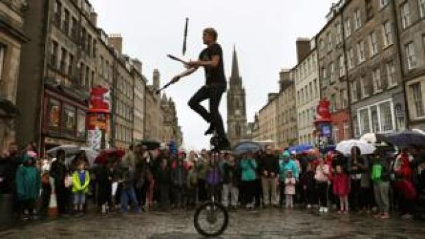 Street performer juggling knives and fire on the Royal Mile