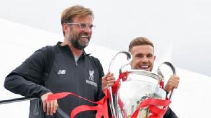 Jurgen Klopp and Jordan Henderson hold aloft the cup as they come out of the plane at Liverpool Airport