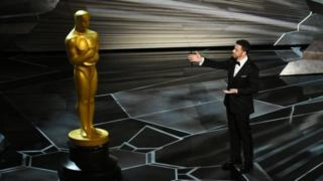 Jimmy Kimmel stands next to a giant Oscars statue