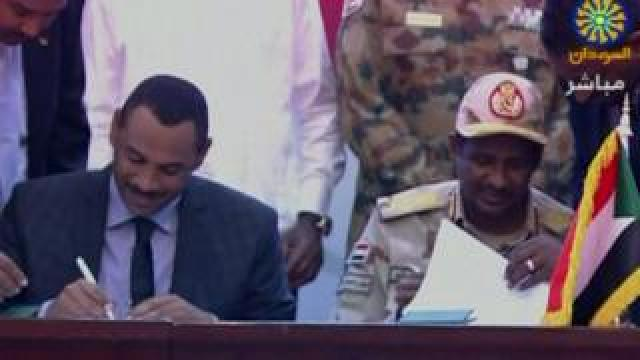 Ahmed al-Rabie and Hemeti sign the deal