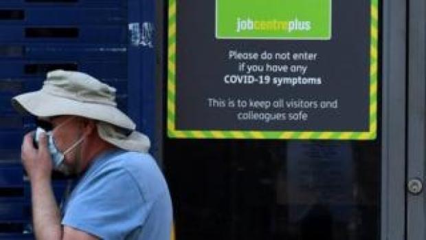 A man wearing a face mask walking past a Job Centre
