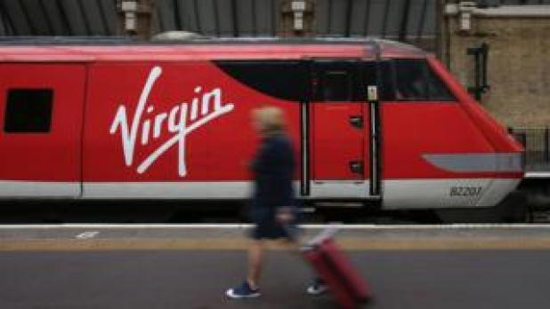 A passenger walking with a suitcase alongside a Virgin train