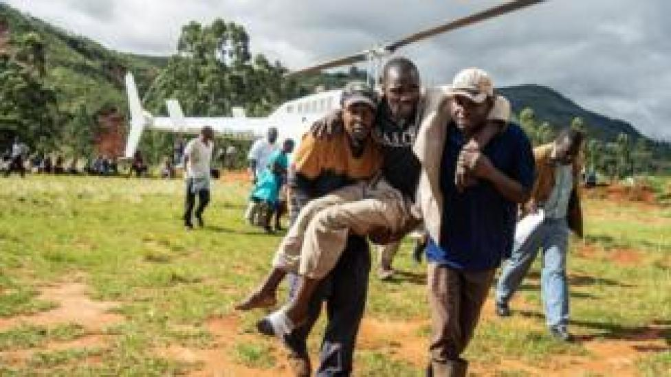 A man injured in the cyclone in Zimbabwe is carried away from a helicopter.