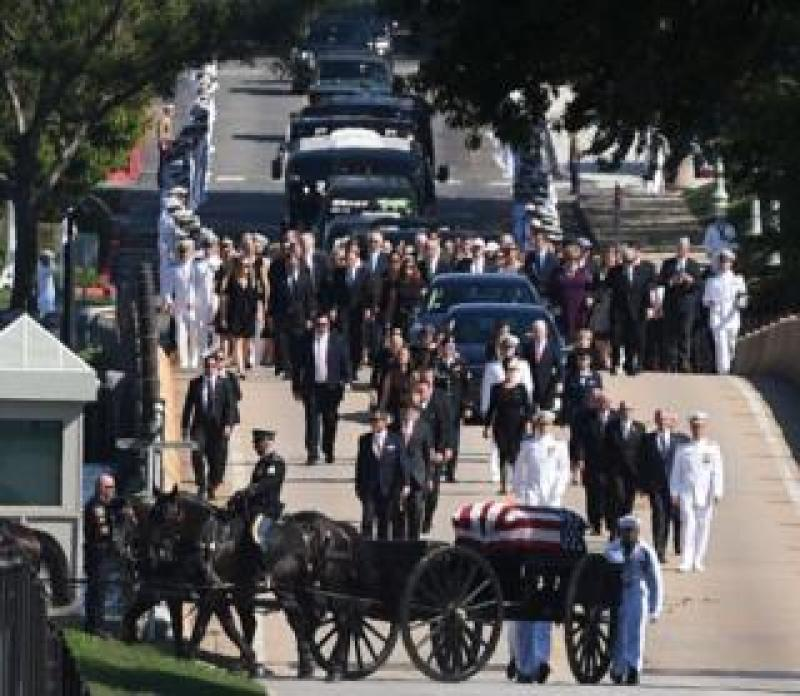 The funeral procession of the late Senator John McCain heads to the cemetery for a private burial at the US Naval Academy in Annapolis