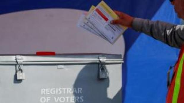 An election worker places mail-in ballots into an election box