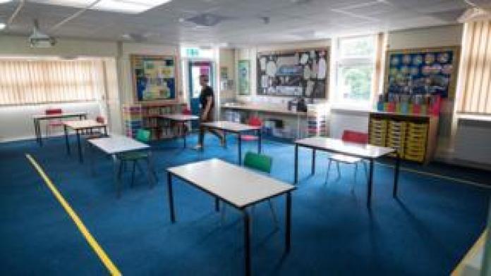 A school head teacher in an empty classroom