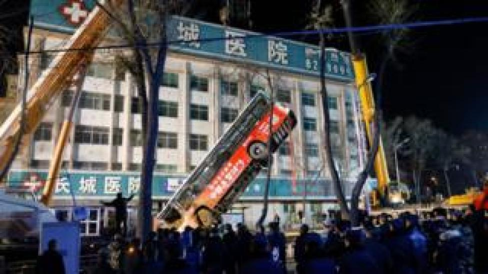 Rescuers lift a bus out of a sinkhole