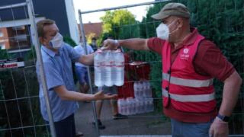 Workers hand out supplies to residents quarantined in Gutersloh