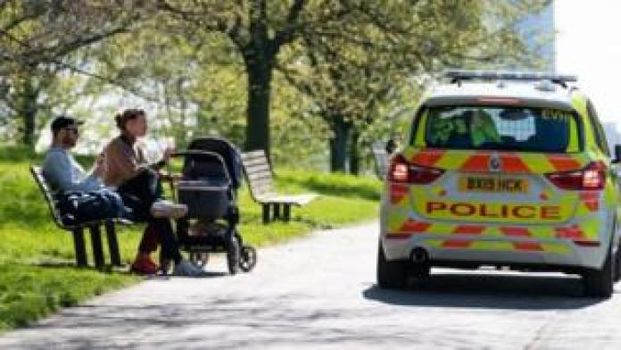 A police car near two people with a baby carriage sitting on a bench