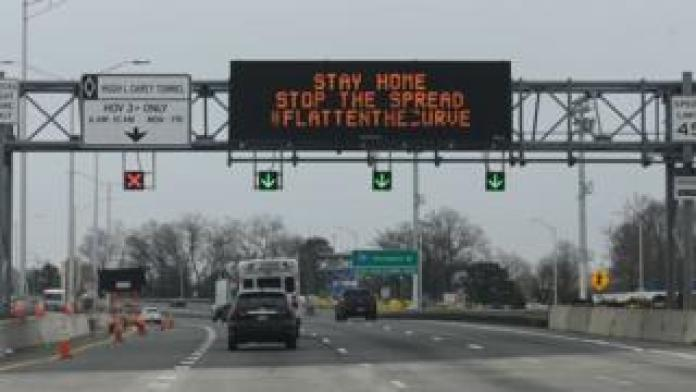 Cars drive under an electronic sign warning drivers of the coronavirus, COVID-19, on a highway near the Verrazano Bridge on March 30, 2020 in New York.