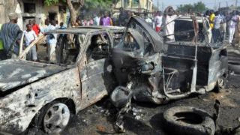 People gather to look at a burnt vehicles at the site of a bomb explosion that rocked the busiest roundabout near the crowded Monday Market in Maiduguri, Borno State, on July 1, 2014.