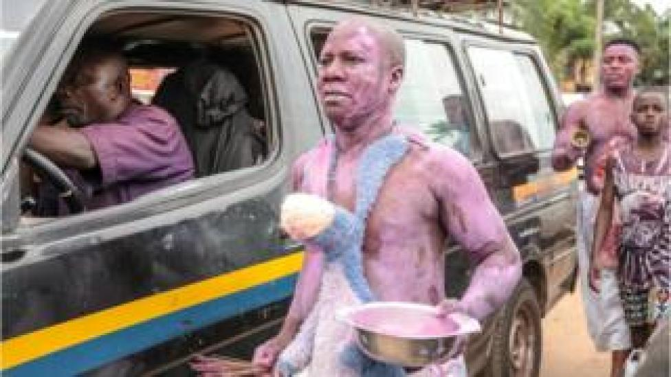 Men covered in purple paint walking next to a car in a street parade in Arondizuogu during the Ikeji Festival in Nigeria