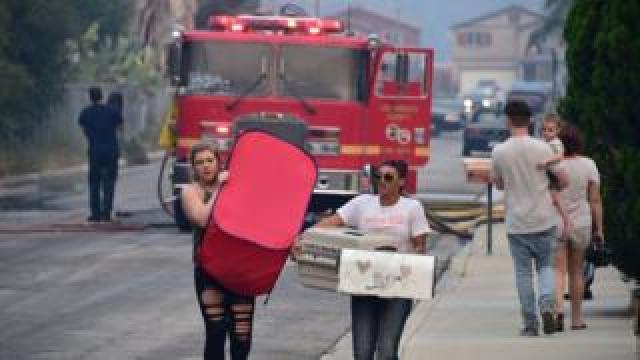 Residents carry belongings in Lake Elsinore, California, south-east of Los Angeles, on August 10, 2018