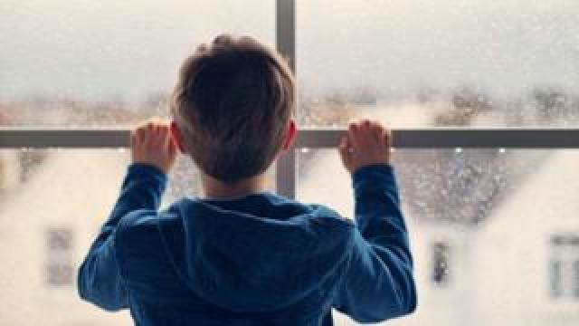 Boy stands at a window
