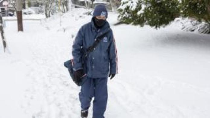 A postman, wrapped up, walks through snow in one community