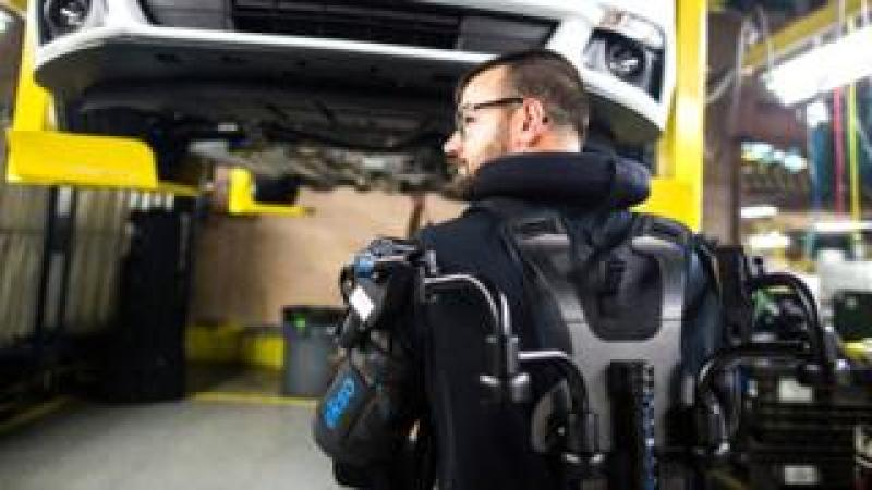 A Ford factory worker wearing a robotic exosuit