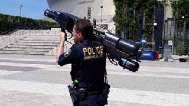 "A New Orleans police officer shoulders a drone capture ""gun"""