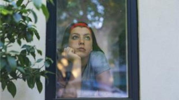 teenage girl looks out of a window