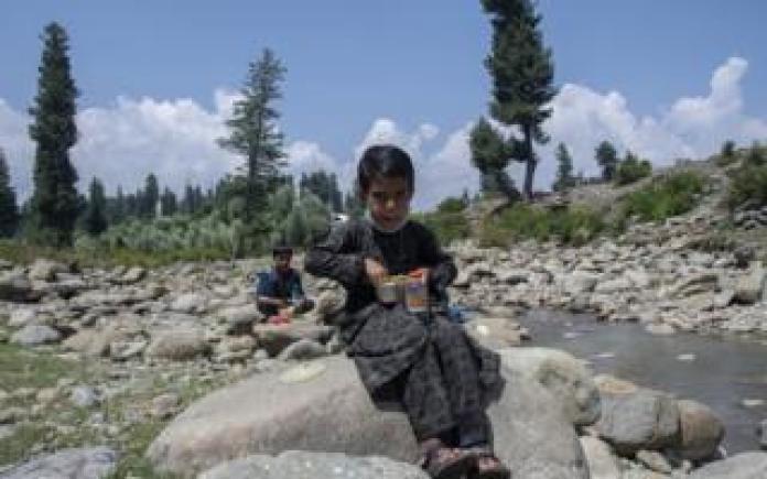 A boy eats his lunch sitting on a rock near a stream.