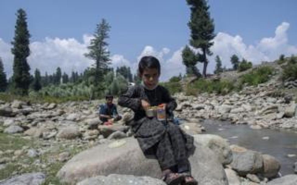 A boy eats lunch sitting on a rock by a stream.