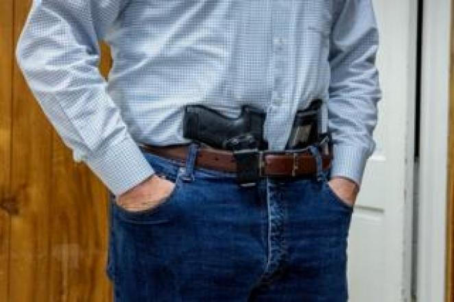A handgun and spare magazines tucked in a waistband at a militia meeting in Virginia