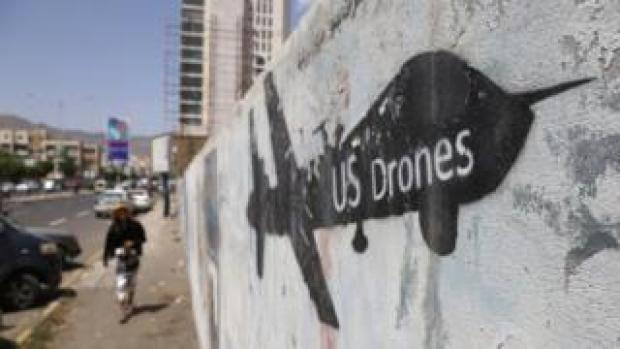A Yemeni man looks at graffiti protesting against US drone strikes on September 19, 2018