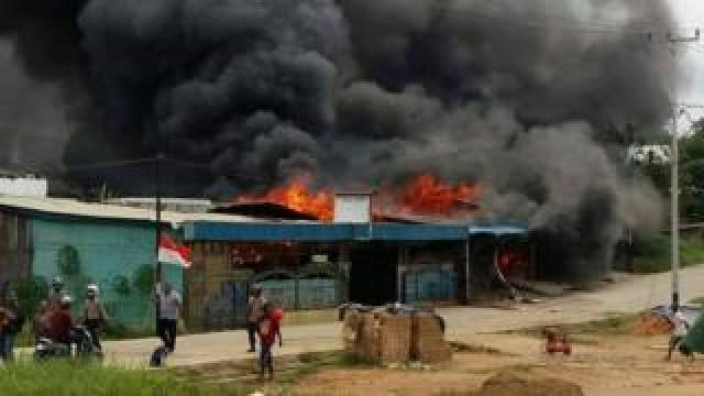 A building, set on fire by rioting demonstrators, is seen in Sorong