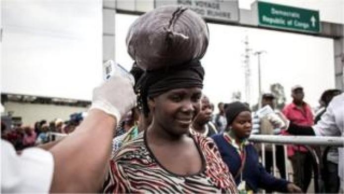 Una mujer mide su temperatura en una estación de detección de ébola cuando ingresa a Ruanda desde la República Democrática del Congo