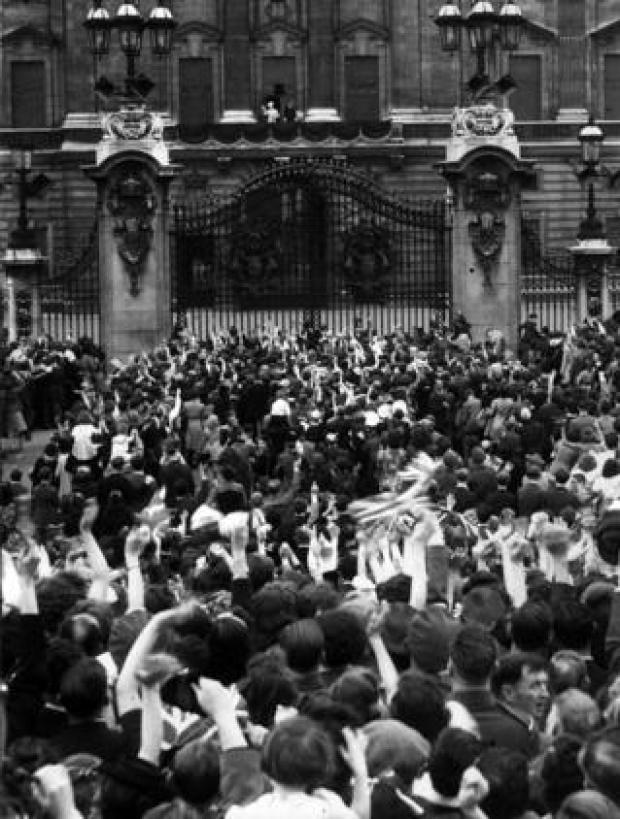 Crowds outside Buckingham Palace cheer on VE Day