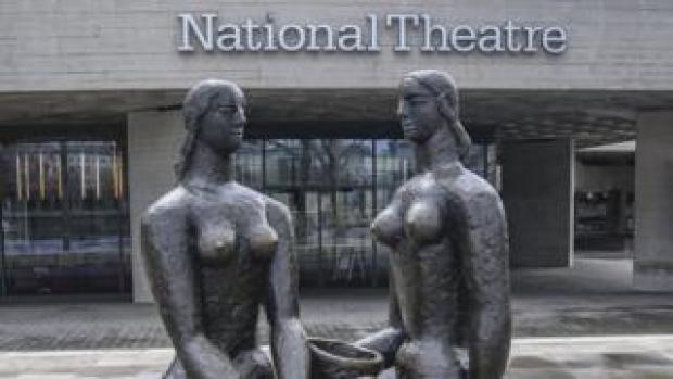 A statue of two women outside the front of the National Theatre