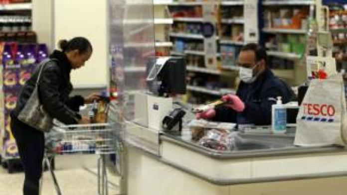 Tesco supermarket cashier wearing protective mask and gloves helps buyer behind plastic screen