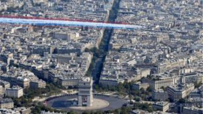 Alpha Jets overflying the capital with plumes of smoke in the colours of the French flag