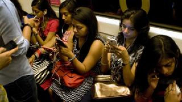Women listen to smartphones on the metro in Delhi
