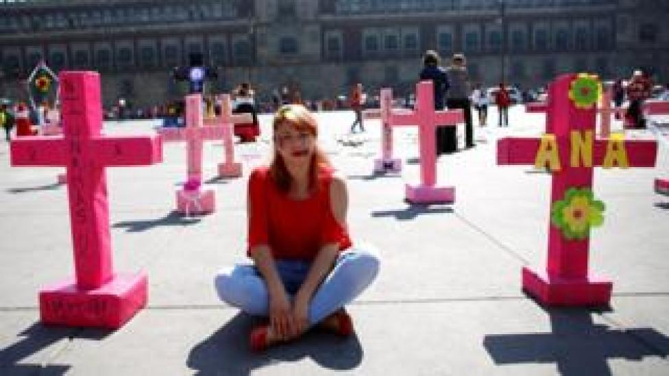 A woman sits among pink crosses during the