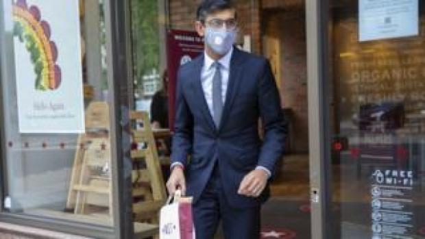 Rishi Sunak wearing a mask buying takeaway food