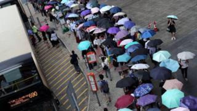 Stranded passengers queue for a shuttle bus