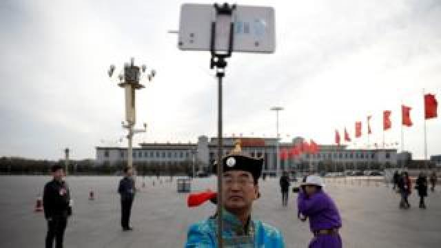 An ethnic minority man poses for a selfie on Tiananmen Square outside the Great Hall of the People ahead of the opening session of the National People's Congress in Beijing, 5 March