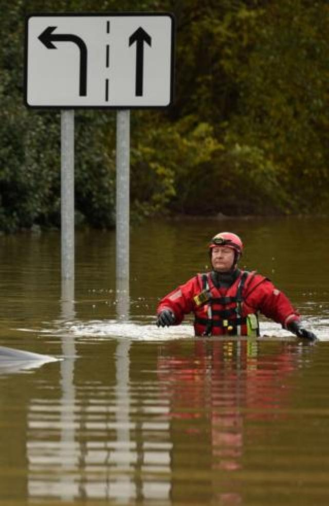 A member of the Fire and Rescue service wades through flood water