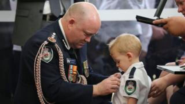 New South Wales Rural Fire Service (NSW RFS) shows RFS Commissioner Shane Fitzsimmons (L) pinning a medal on Harvey Keaton