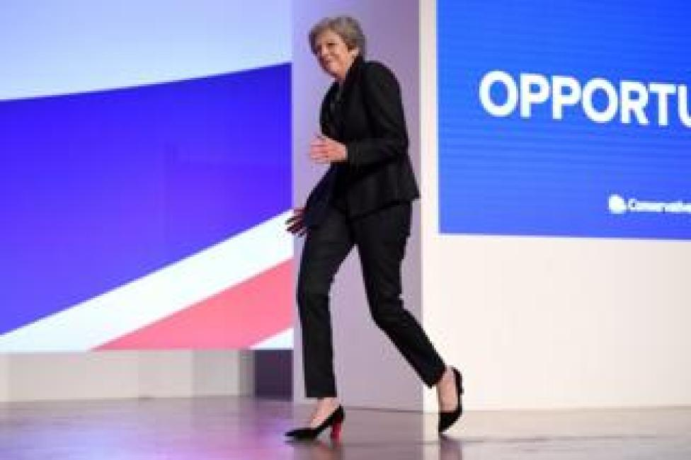 British Prime Minister Theresa May dances as she walks out onto the stage