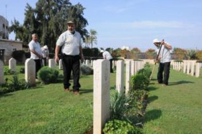 Members of the Jaradah family work to monitor laws and flowers at the Gaza cemetery.
