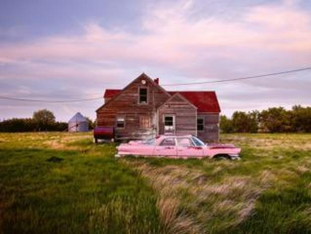 Cars: An abandoned pink car in front of a wooden house