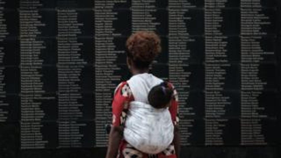 Woman looking at list of Rwanda genocide victims