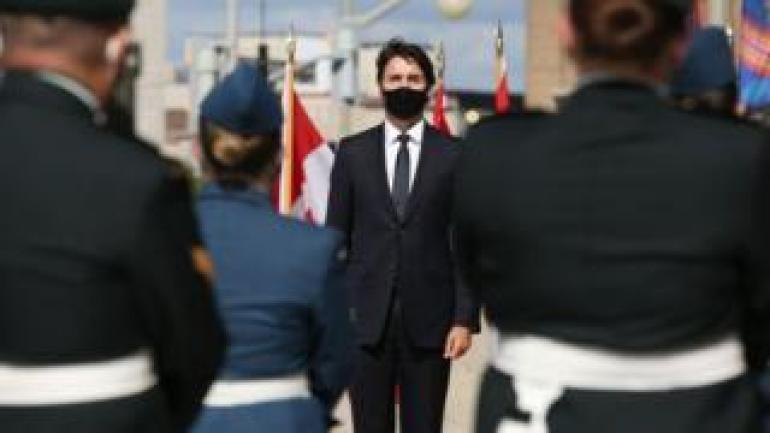 Canada's Prime Minister Justin Trudeau listens to the National Anthem prior to the Speech from the Throne on September 23, 2020, in Ottawa, Canada