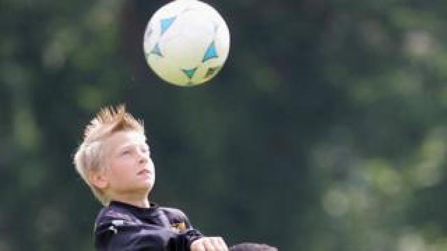 boy heading football